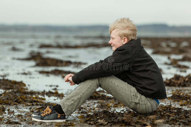 Garçon de l'adolescence de sourire s'asseyant sur la plage pendant la marée basse photos libres de droits