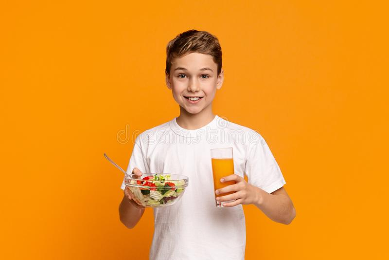Garçon de l'adolescence dinant avec de la salade et le jus de légume frais photo stock