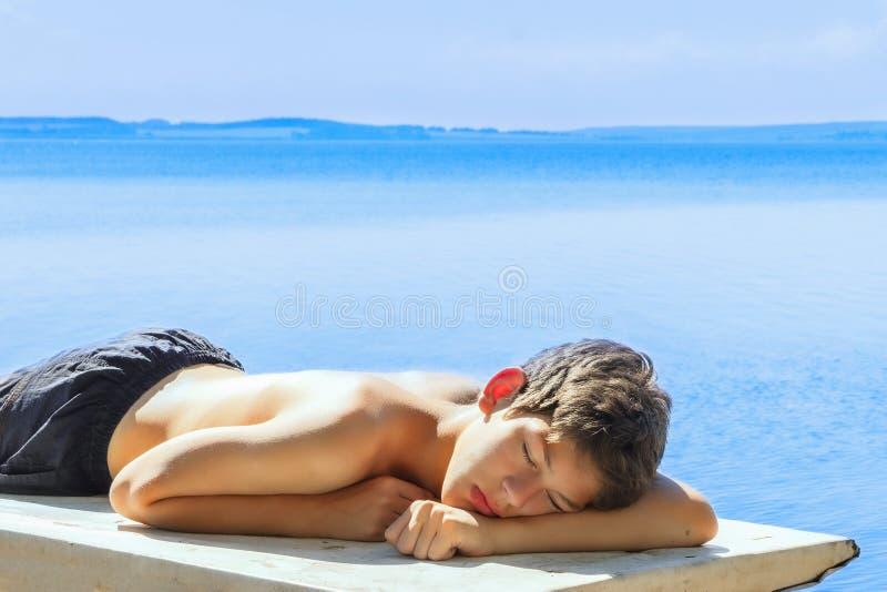 Garçon de l'adolescence dormant sur la plage Vacances d'école dehors photos stock