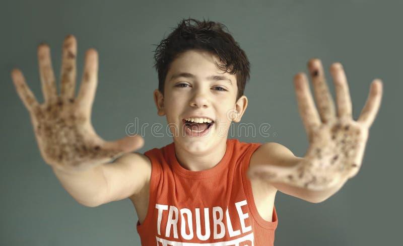 Garçon de l'adolescence malfaisant avec le sourire sale de main photo stock