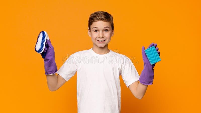 Garçon de l'adolescence mignon dans les gants en caoutchouc tenant l'éponge et la brosse image stock
