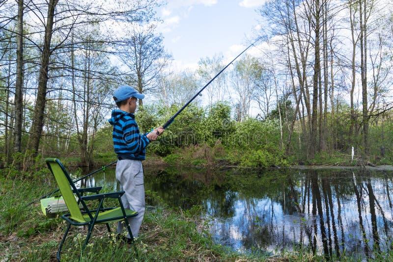 Garçon de l'adolescence pêchant un poisson avec la canne à pêche sur la plage de lac photos stock