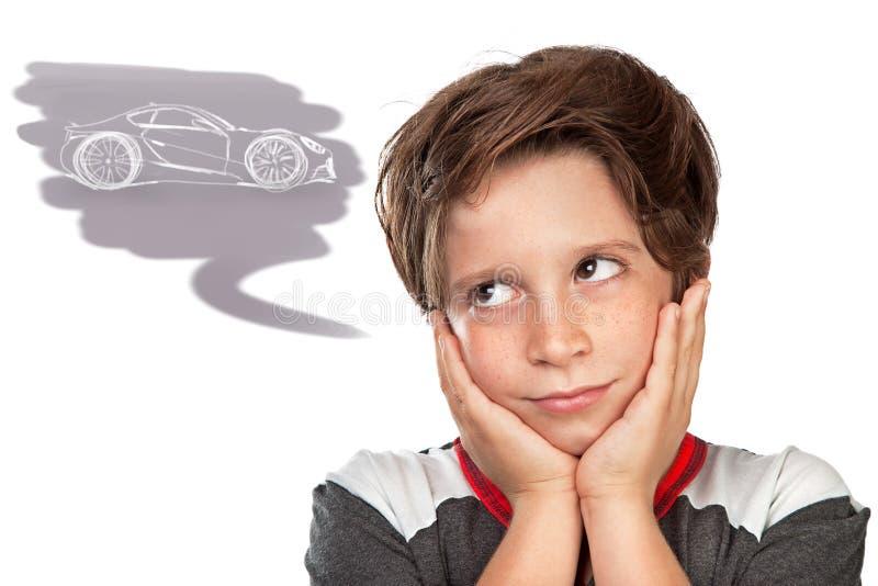 Garçon de l'adolescence rêvant d'une voiture photo stock