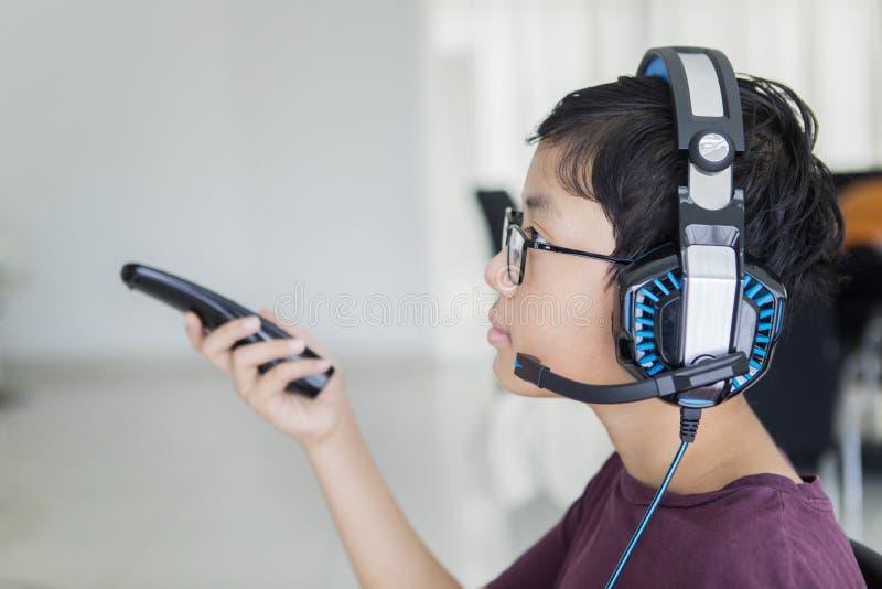 Garçon de l'adolescence regardant la TV avec des écouteurs photographie stock libre de droits
