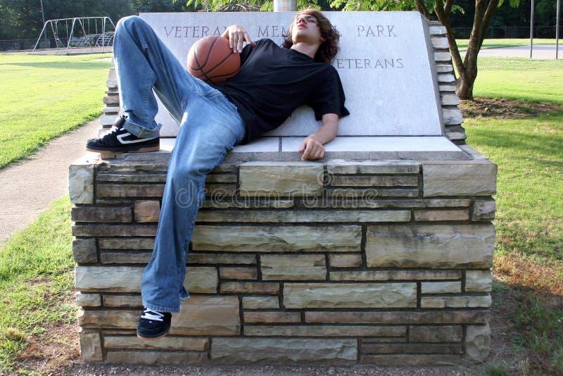 Garçon de l'adolescence se reposant après match de basket photos stock