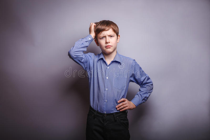 Garçon de l'adolescence tenant sa main sur la pensée profonde principale photo stock