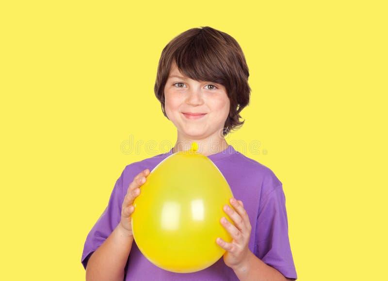 Garçon de la préadolescence adorable avec un ballon jaune images libres de droits