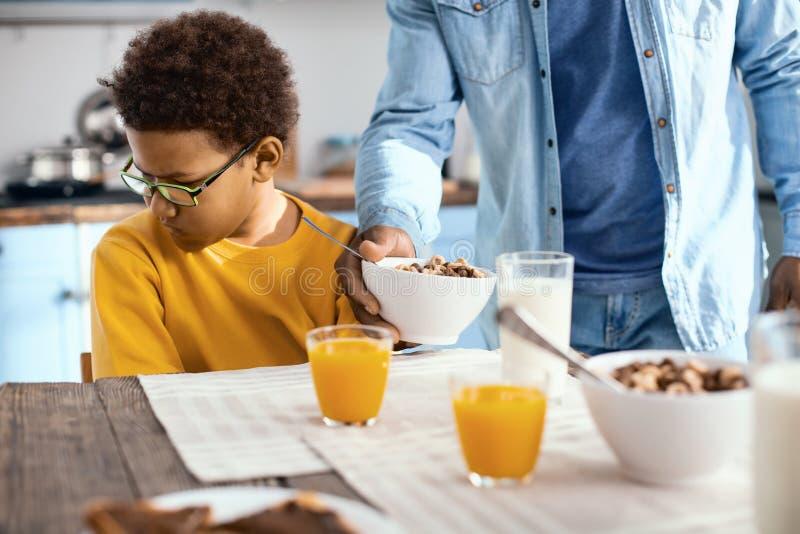 garçon de la préadolescence aux cheveux bouclés ne voulant pas manger des céréales image libre de droits