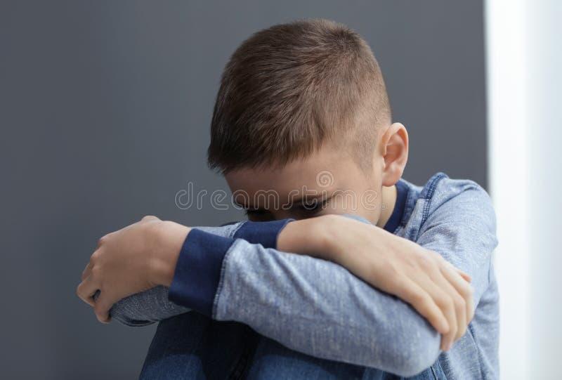 Garçon de la préadolescence bouleversé s'asseyant au mur gris photo libre de droits