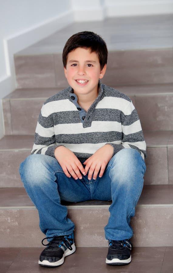 Garçon de la préadolescence s'asseyant sur les escaliers photo stock