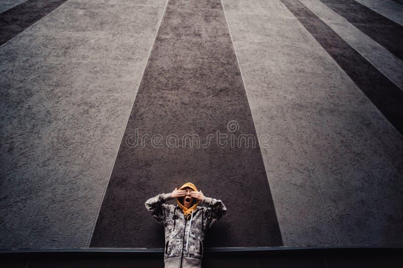 Garçon de la préadolescence sur une rue dans une grande ville à côté seul d'un gratte-ciel images stock