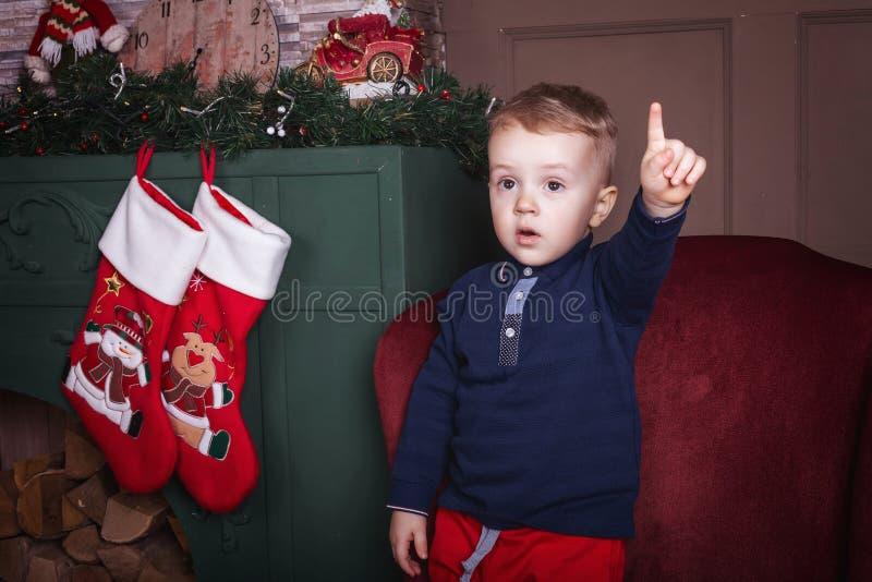 Garçon de Litlittle soulevant le doigt près du fond de Noël photographie stock