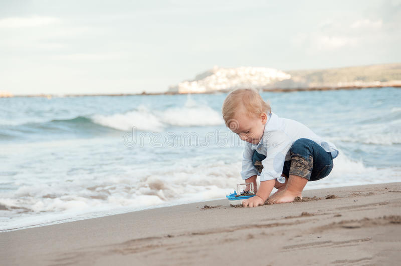 Garçon de Litlle jouant sur la plage avec un bateau Vacances d'été et photo libre de droits