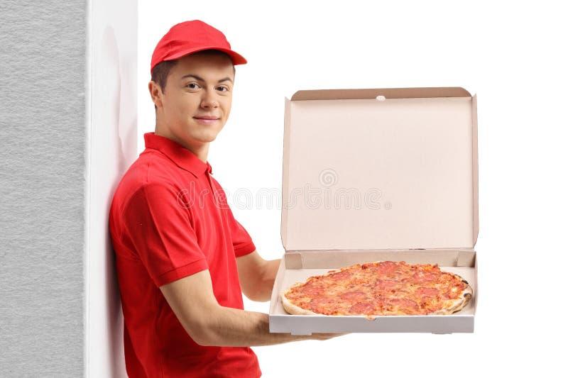 Garçon de livraison de pizza se penchant sur un mur et montrant une boîte avec la pizza photographie stock