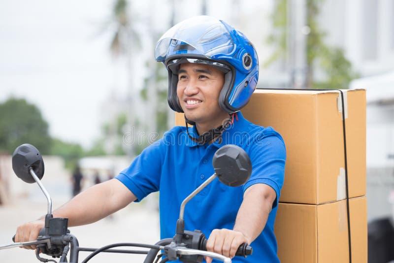 Garçon de livraison sur la moto avec la boîte de colis de tronc conduisant pour jeûner dans la précipitation Messager fournissant image stock