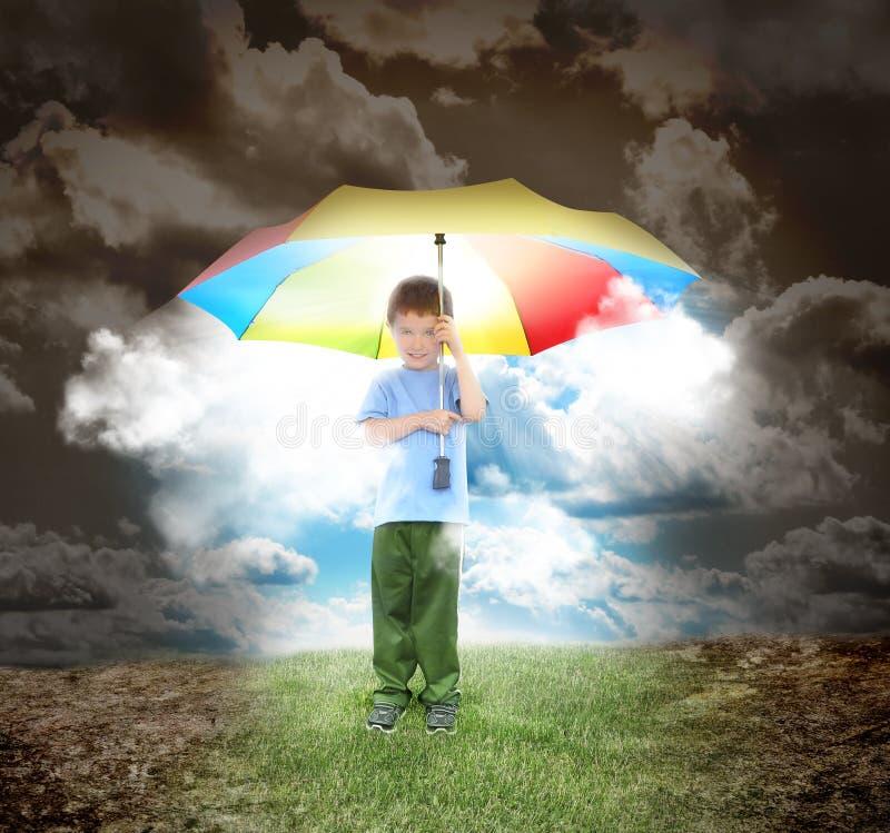 Garçon de parapluie avec des rayons de soleil et d'espoir image libre de droits