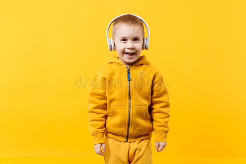 Garçon de petit enfant 3-4 années portant les vêtements jaunes dans des écouteurs d'isolement sur le fond orange de mur, studio d image libre de droits