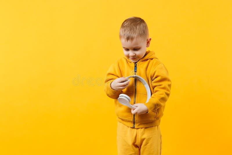 Garçon de petit enfant 3-4 années portant les vêtements jaunes dans des écouteurs d'isolement sur le fond orange de mur, studio d photos stock