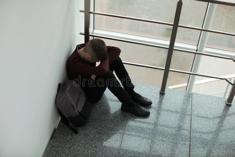 Garçon de renversement avec le sac à dos se reposant près de la fenêtre à l'intérieur photos libres de droits