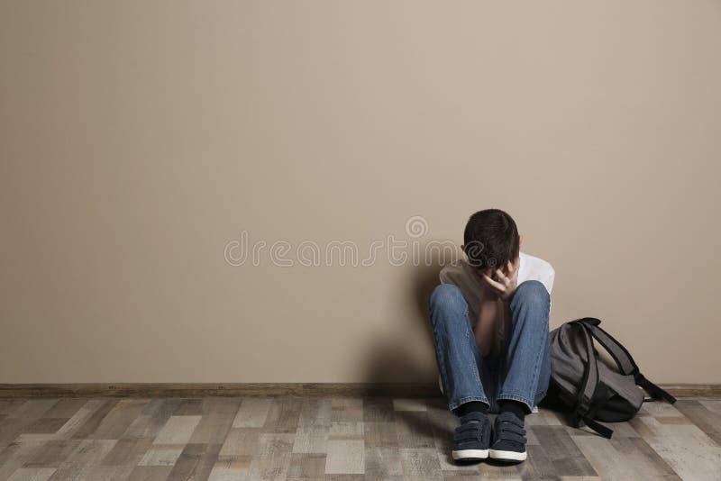 Gar?on de renversement avec le sac ? dos se reposant sur le plancher au mur de couleur l'espace images stock