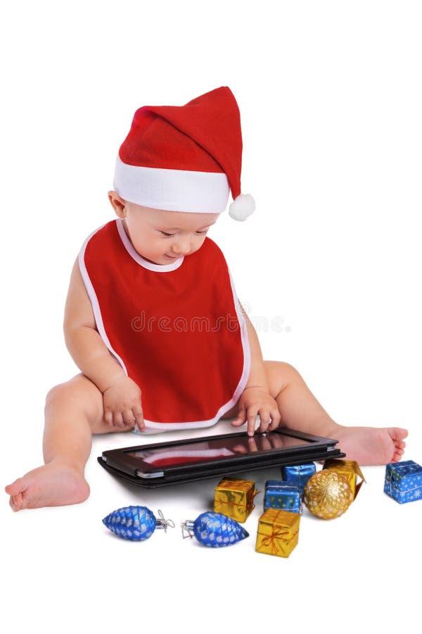 Garçon de Santa recherchant sur un comprimé images stock
