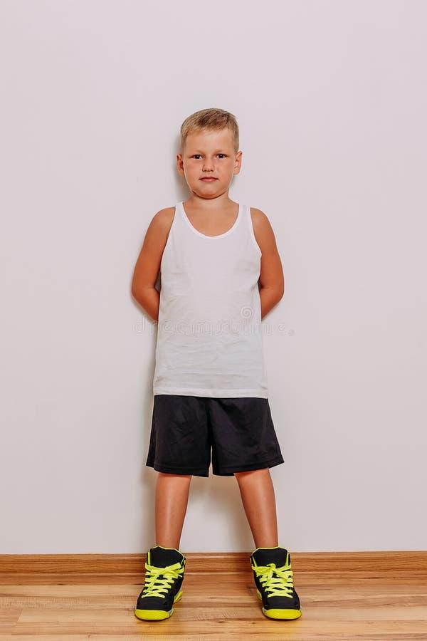 Garçon de sept ans dans un T-shirt blanc, des shorts noirs de basket-ball et des espadrilles sur un fond blanc photos libres de droits