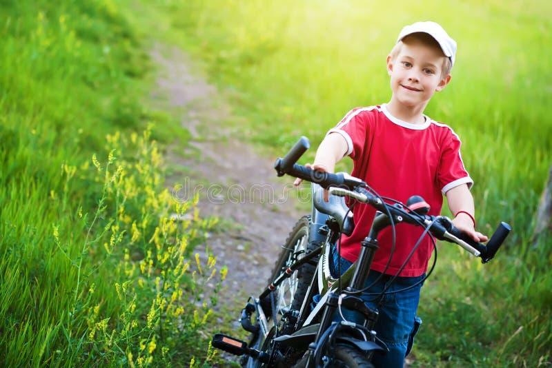 Garçon de six ans recherchant une voie pour faire du vélo images libres de droits