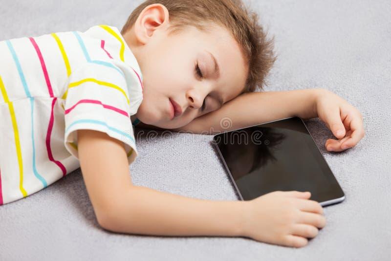 Garçon de sommeil fatigué d'enfant tenant la tablette photographie stock