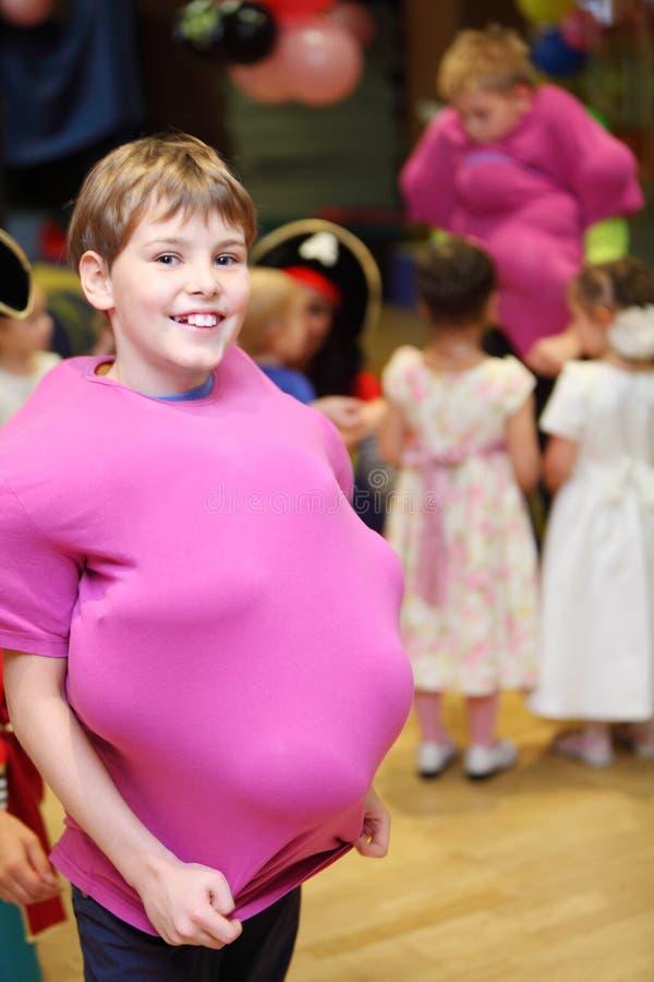 Garçon de sourire avec des ballons à la réception d'enfants. image stock
