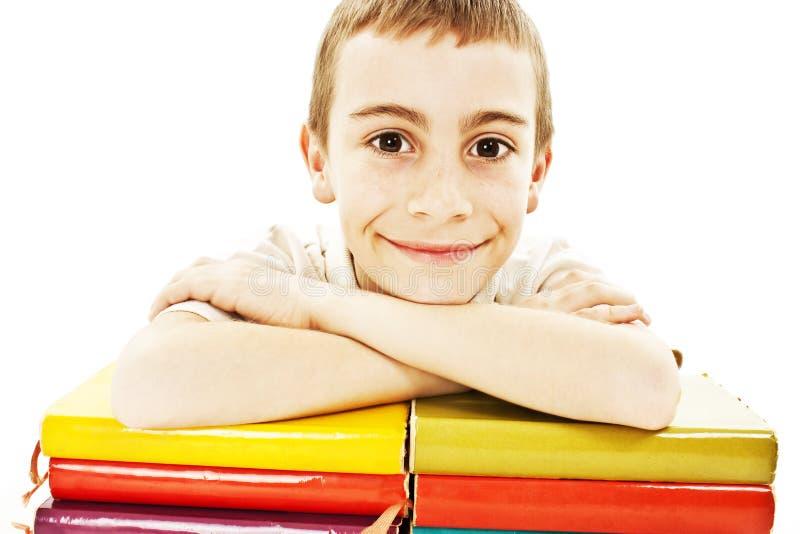 Garçon de sourire avec les livres d'école colorés sur la table photos stock