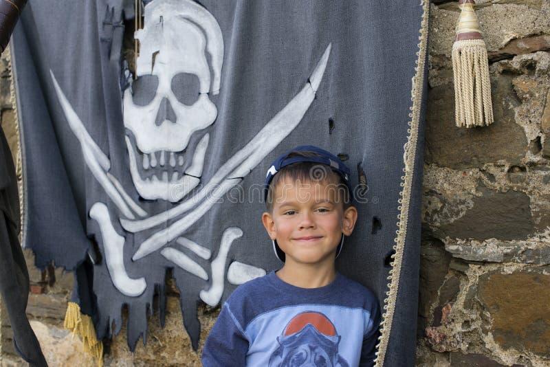 Garçon de sourire contre le contexte d'un drapeau de pirate photo stock