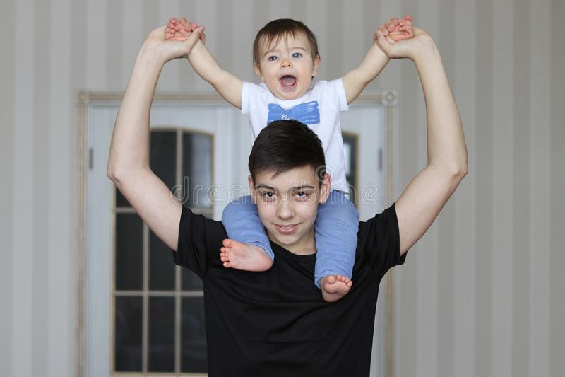 Garçon de sourire d'adolescent tenant son petit frère s'asseyant sur son cou photo stock