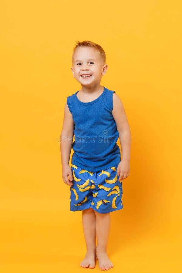 Garçon de sourire d'enfant d'amusement 3-4 années portant les vêtements bleus d'été de plage d'isolement sur le fond jaune-orange photographie stock libre de droits