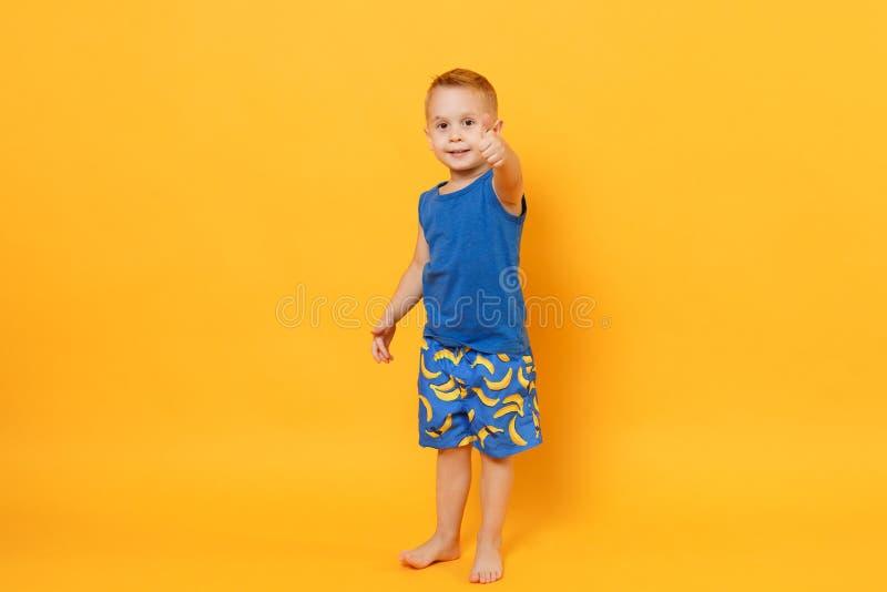 Garçon de sourire d'enfant d'amusement 3-4 années portant les vêtements bleus d'été de plage d'isolement sur le fond jaune-orange photos stock