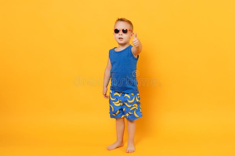 Garçon de sourire d'enfant d'amusement 3-4 années portant les vêtements bleus d'été de plage d'isolement sur le fond jaune-orange photos libres de droits