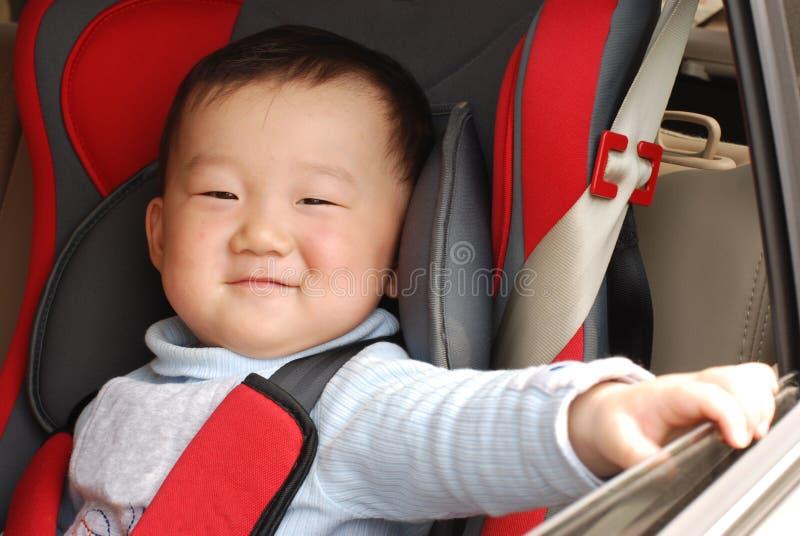 Garçon de sourire dans le siège sûr de chéri du véhicule photographie stock libre de droits