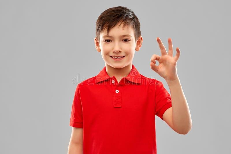 Garçon de sourire dans le signe rouge de main d'ok d'apparence de T-shirt photographie stock libre de droits