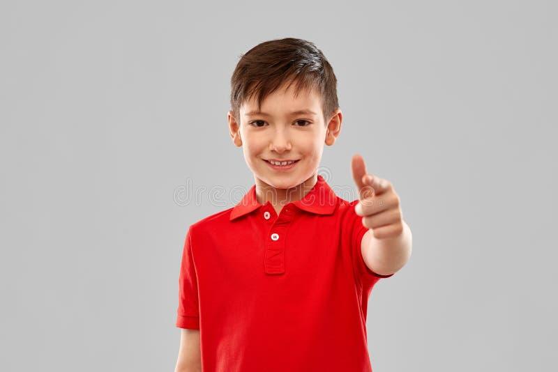 Garçon de sourire dans le T-shirt rouge indiquant le doigt vous photo stock