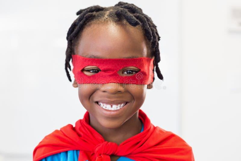 Garçon de sourire feignant pour être un super héros photos stock
