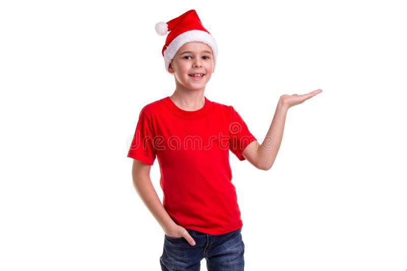 Garçon de sourire mignon, chapeau de Santa sur sa tête, avec la main gauche horizontalement prête pour le cadeau Concept : Noël o photographie stock libre de droits