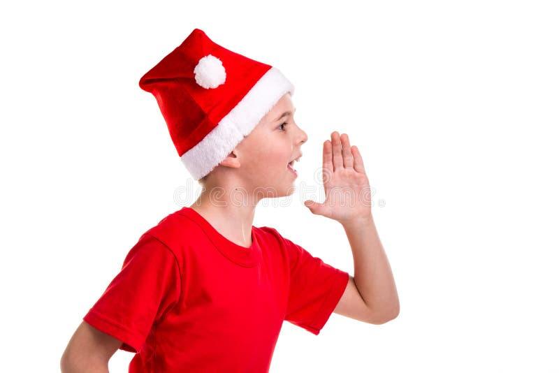 Garçon de sourire mignon, chapeau de Santa sur sa tête, avec la main gauche verticalement, appelant pour Concept : Noël ou nouvea photo libre de droits