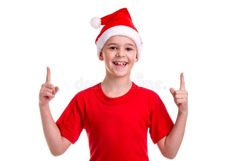 Garçon de sourire mignon, chapeau de Santa sur sa tête, avec les doigts de pointage  Concept : Noël ou vacances de bonne année photos libres de droits