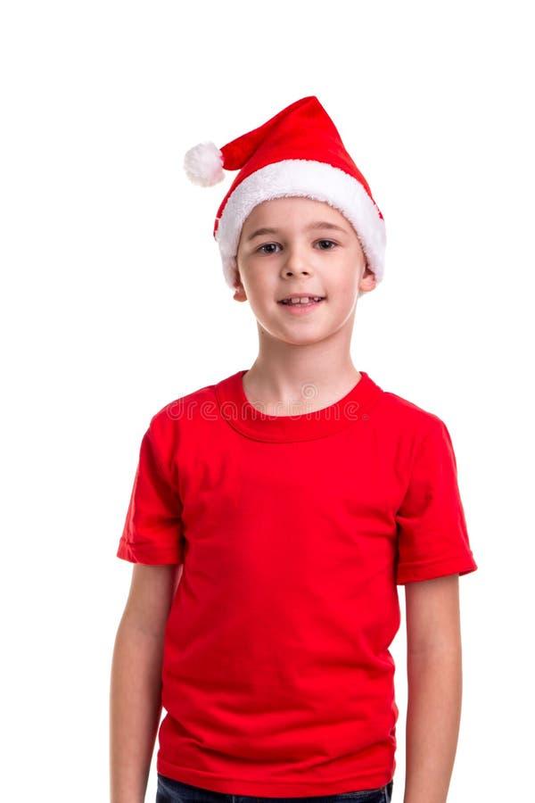 Garçon de sourire mignon, chapeau de Santa sur sa tête Concept : Noël ou vacances de bonne année photos stock