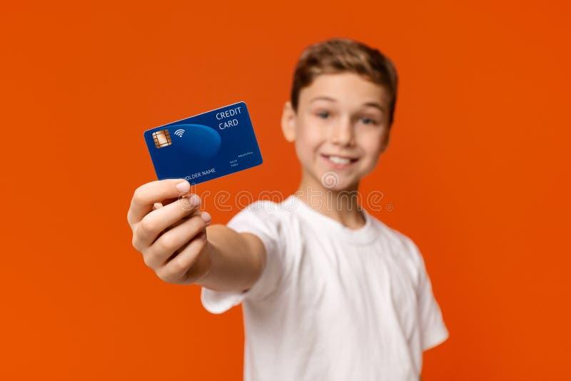 Garçon de sourire montrant la carte de crédit à la caméra images libres de droits