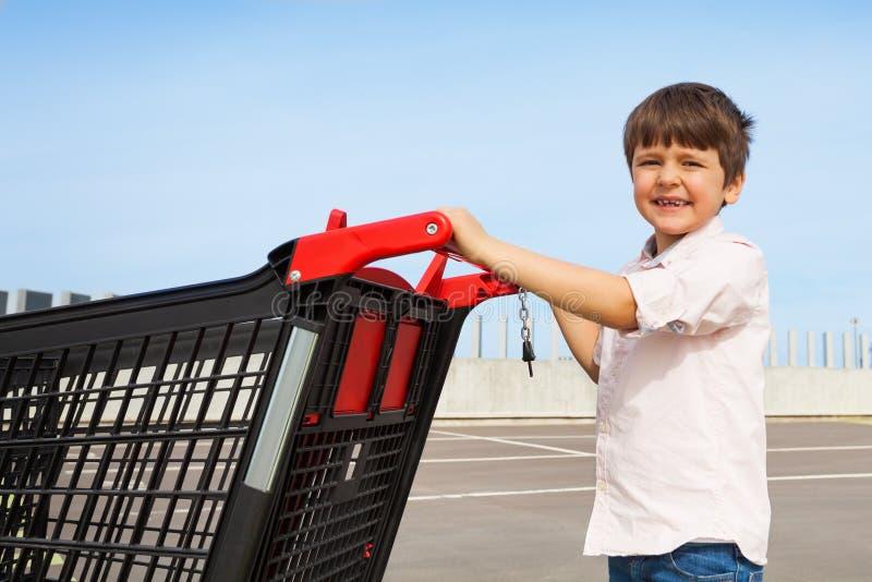 Garçon de sourire poussant le caddie au supermarché photo libre de droits