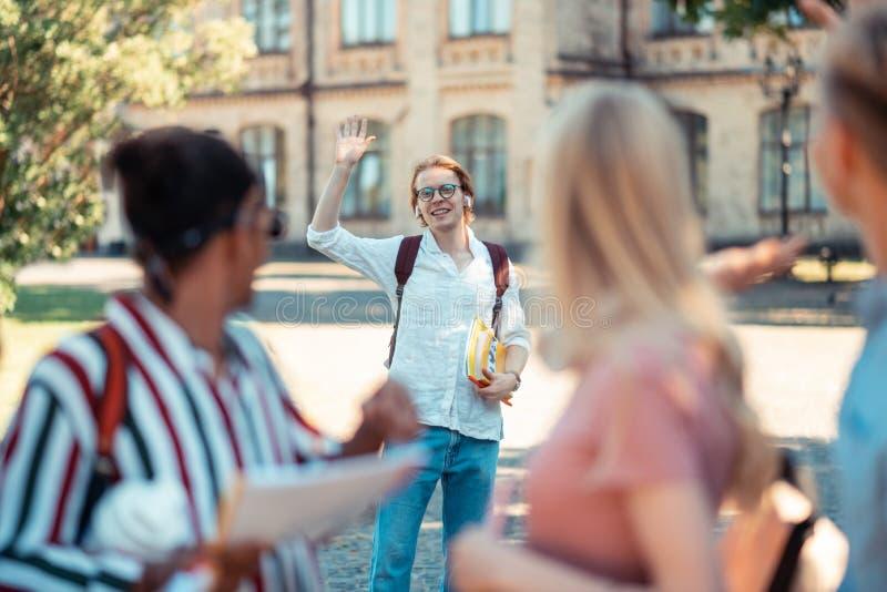 Garçon de sourire saluant ses groupmates dans la cour photos libres de droits