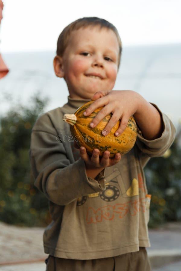 Garçon de sourire se tenant avec le grand potiron jaune dans des mains image stock