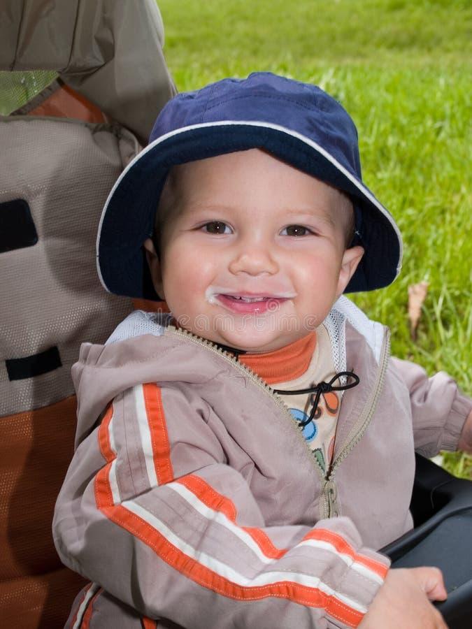 Garçon de sourire souillé par le lait photographie stock