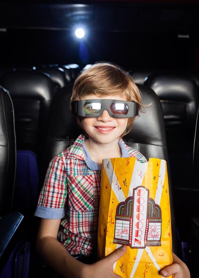 Garçon de sourire tenant le maïs éclaté dans le théâtre 3D photos libres de droits