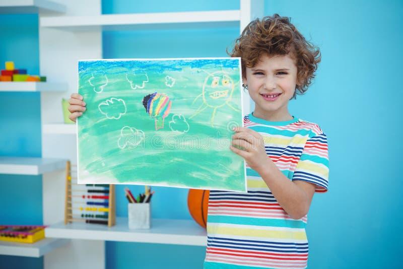 Garçon de sourire tenant une photo photographie stock libre de droits